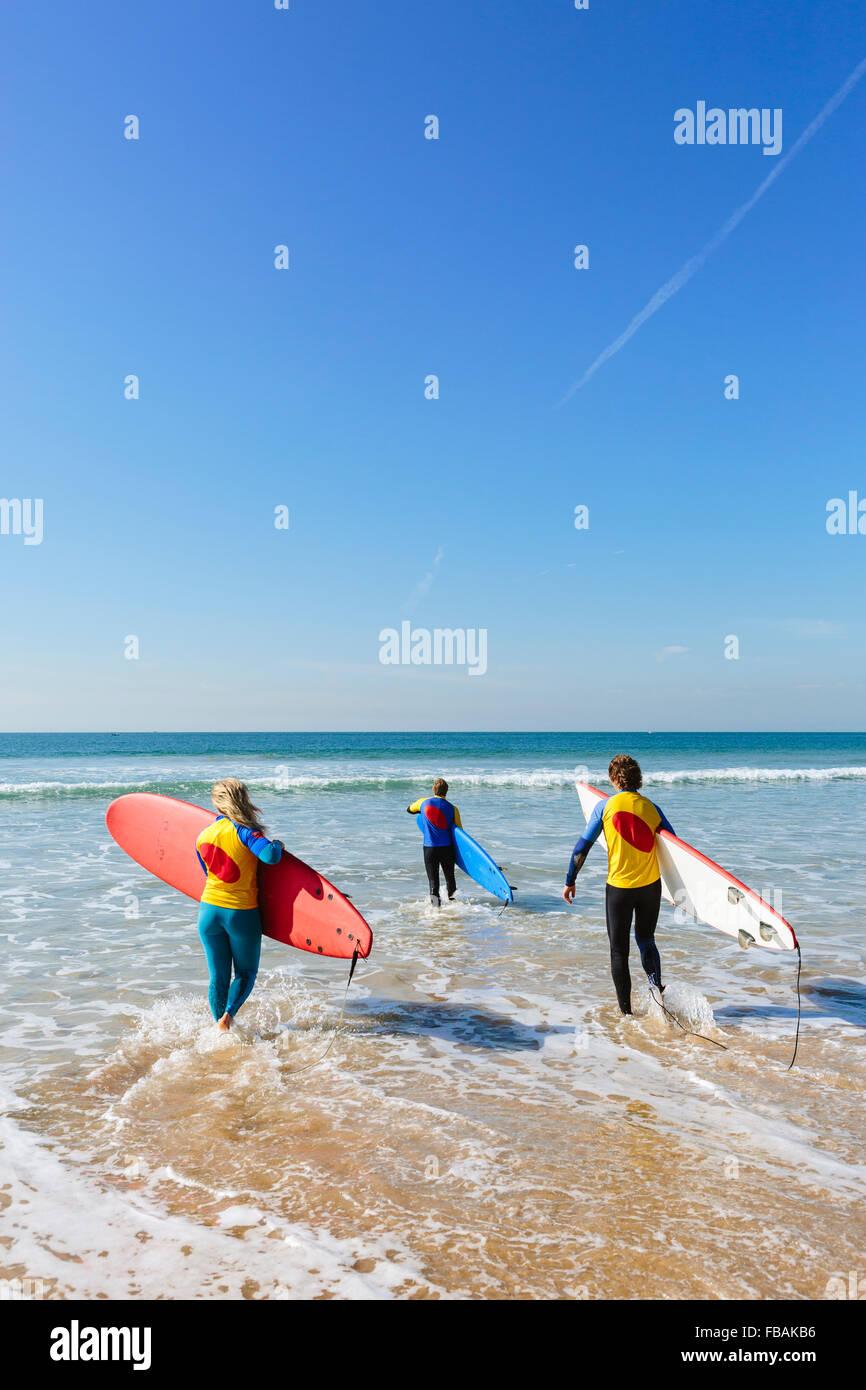 Il Portogallo, Lisbona, tre persone che trasportano le tavole da surf Immagini Stock
