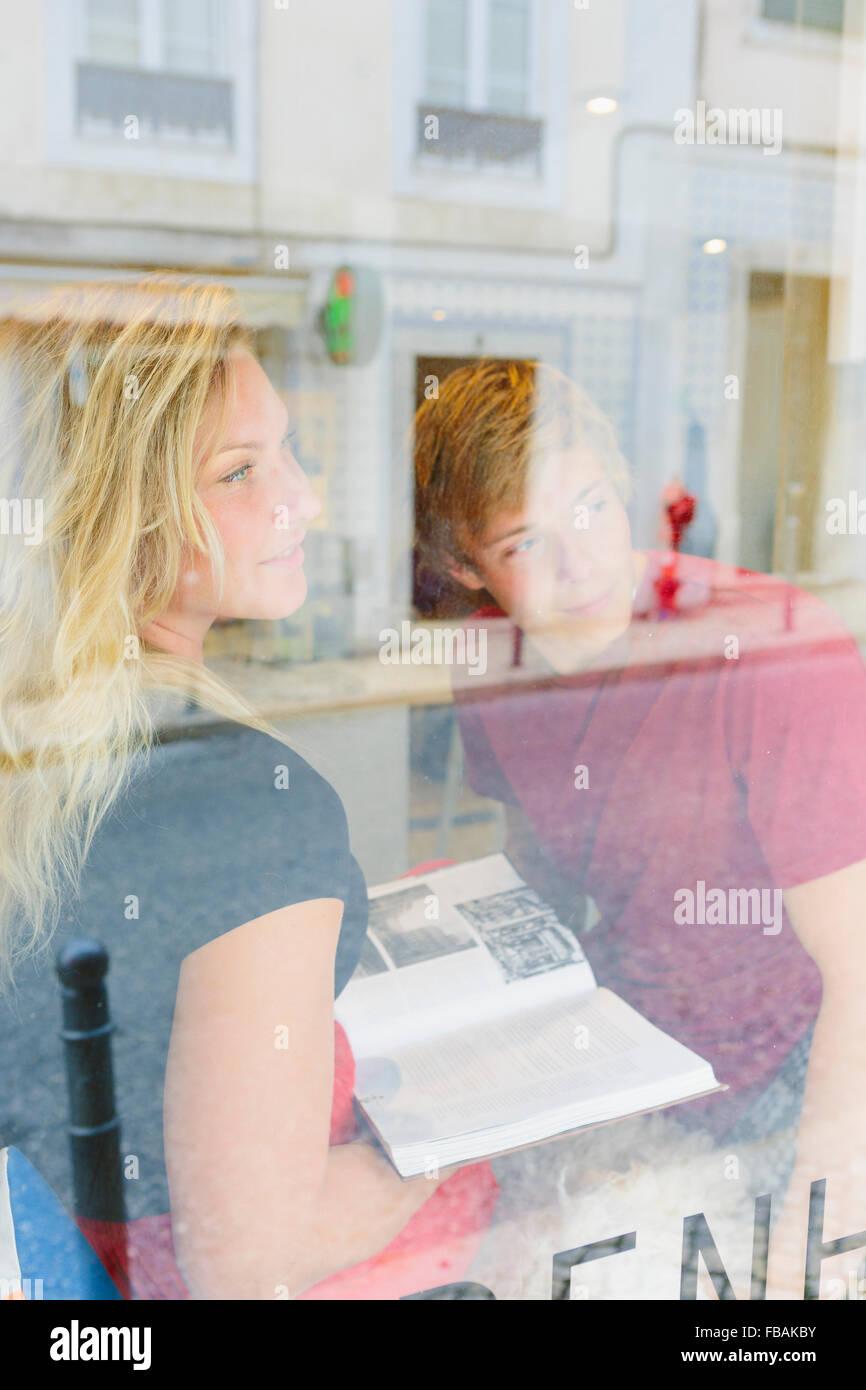 Il Portogallo, Lisbona, due persone guardando attraverso la finestra Immagini Stock