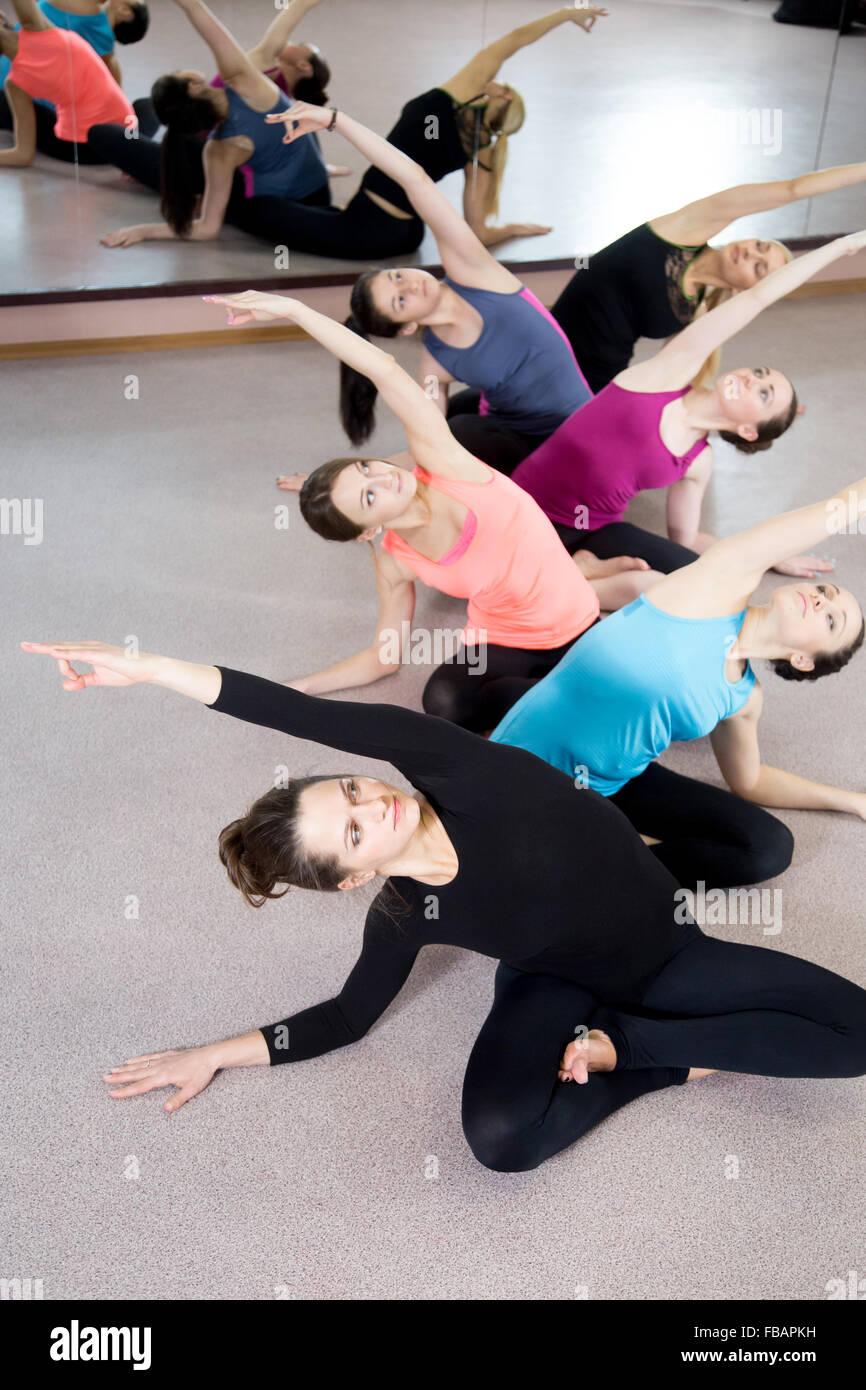 Team sportivo di yogi ragazze nella classe di Yoga asana seduti con le gambe incrociate, piegatura, facendo esercizi Immagini Stock