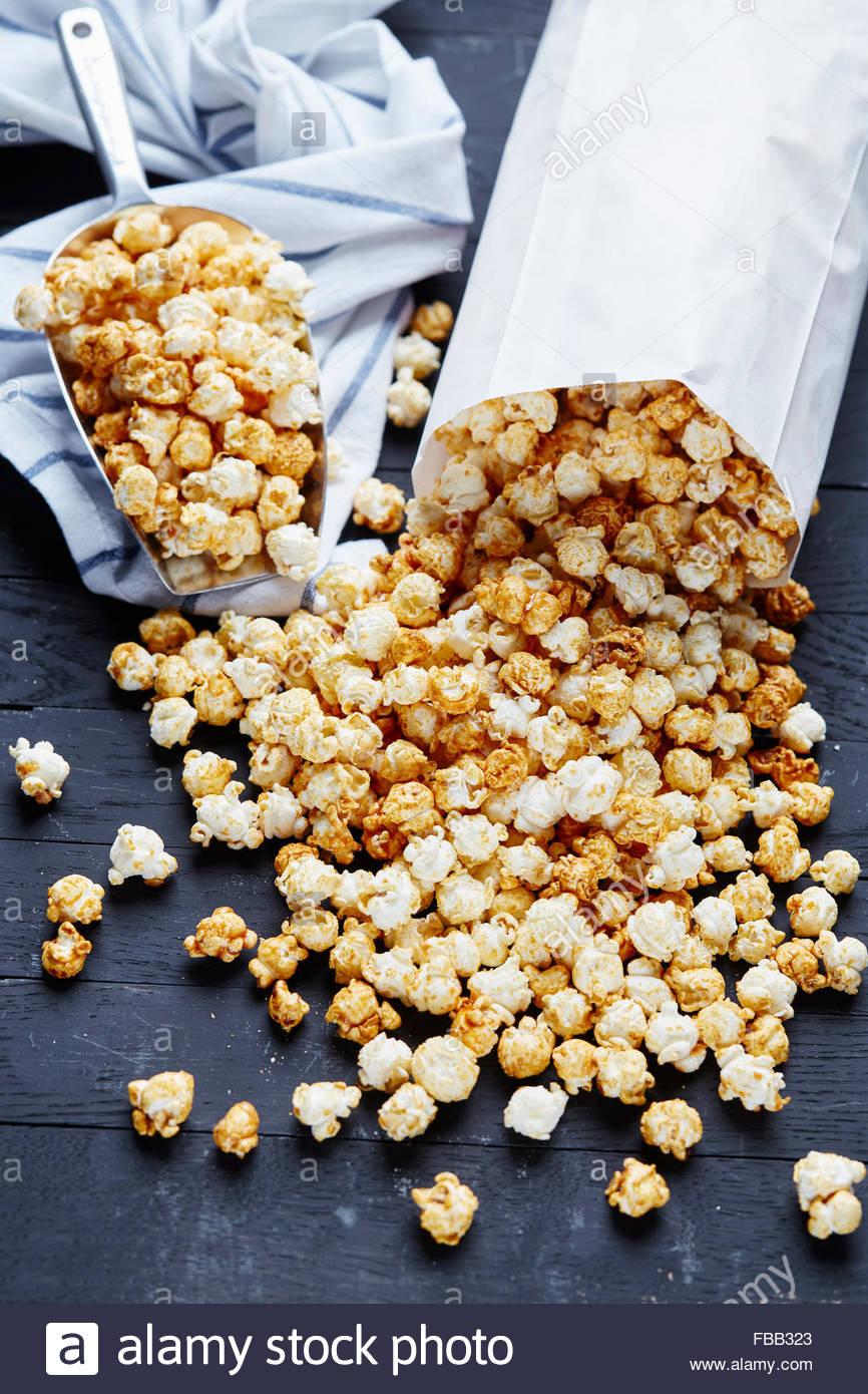 Sacchetto di carta e metallo scoop pieno di popcorn su sfondo nero Foto Stock