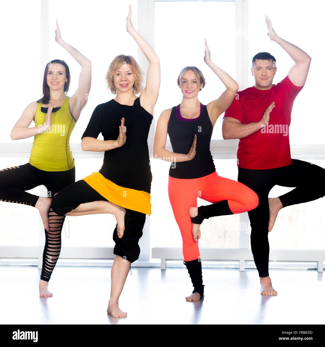 Un gruppo di quattro persone contente e fare yoga formazione in classe, in piedi in asana, albero pongono, vrikshasana Immagini Stock