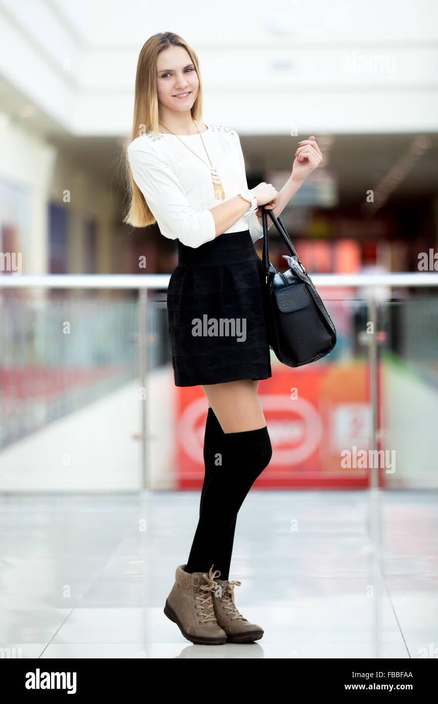 ac1afee14d9a Snello giovane donna in carino vestito alla moda per lo shopping, in  ufficio o in studio. Shopper ragazza camminare in breve gonna nera e il  ginocchio di ...