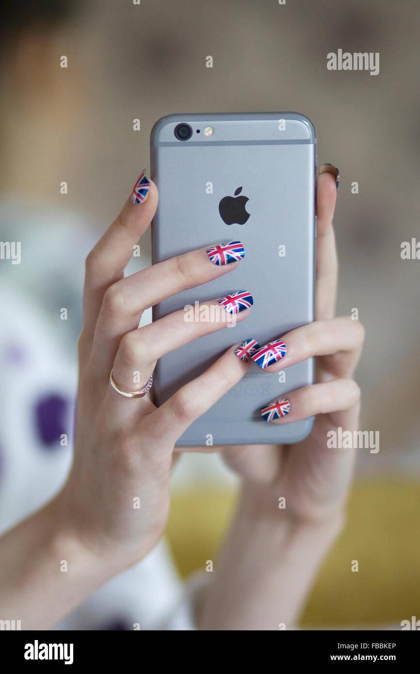 Mani di Apple i Phone con chiodi verniciato in unione jack Immagini Stock