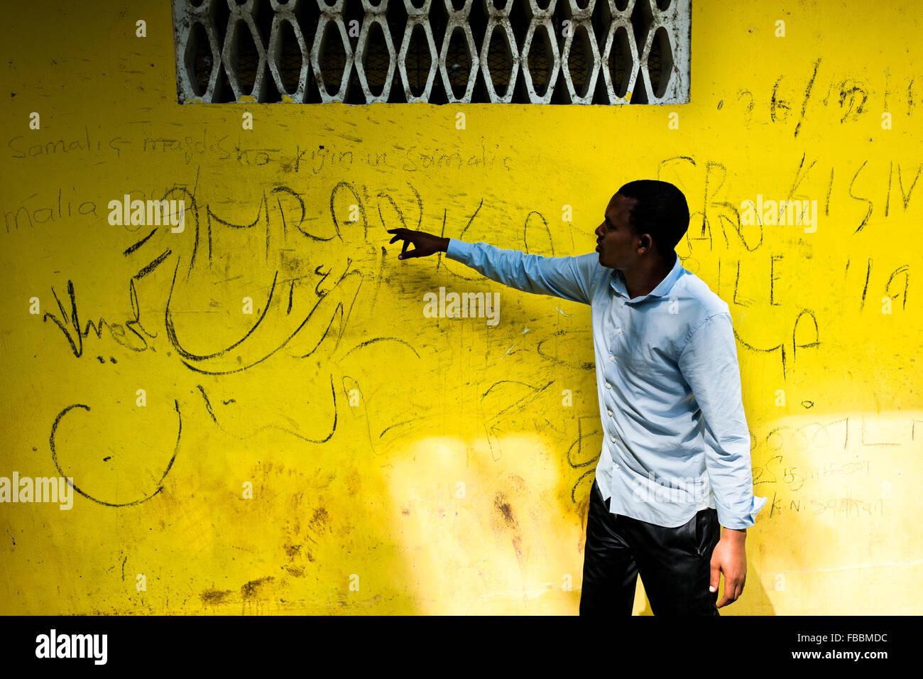 Un giovane immigrato somalo si traduce in arabo script scritti sulla parete del centro di detenzione a Metetí, Immagini Stock