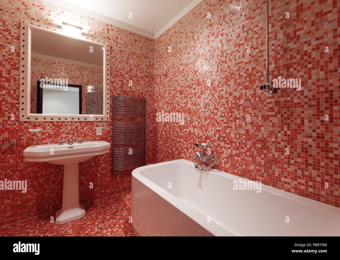 Bagno con piastrelle rosse e una vasca da bagno foto immagine