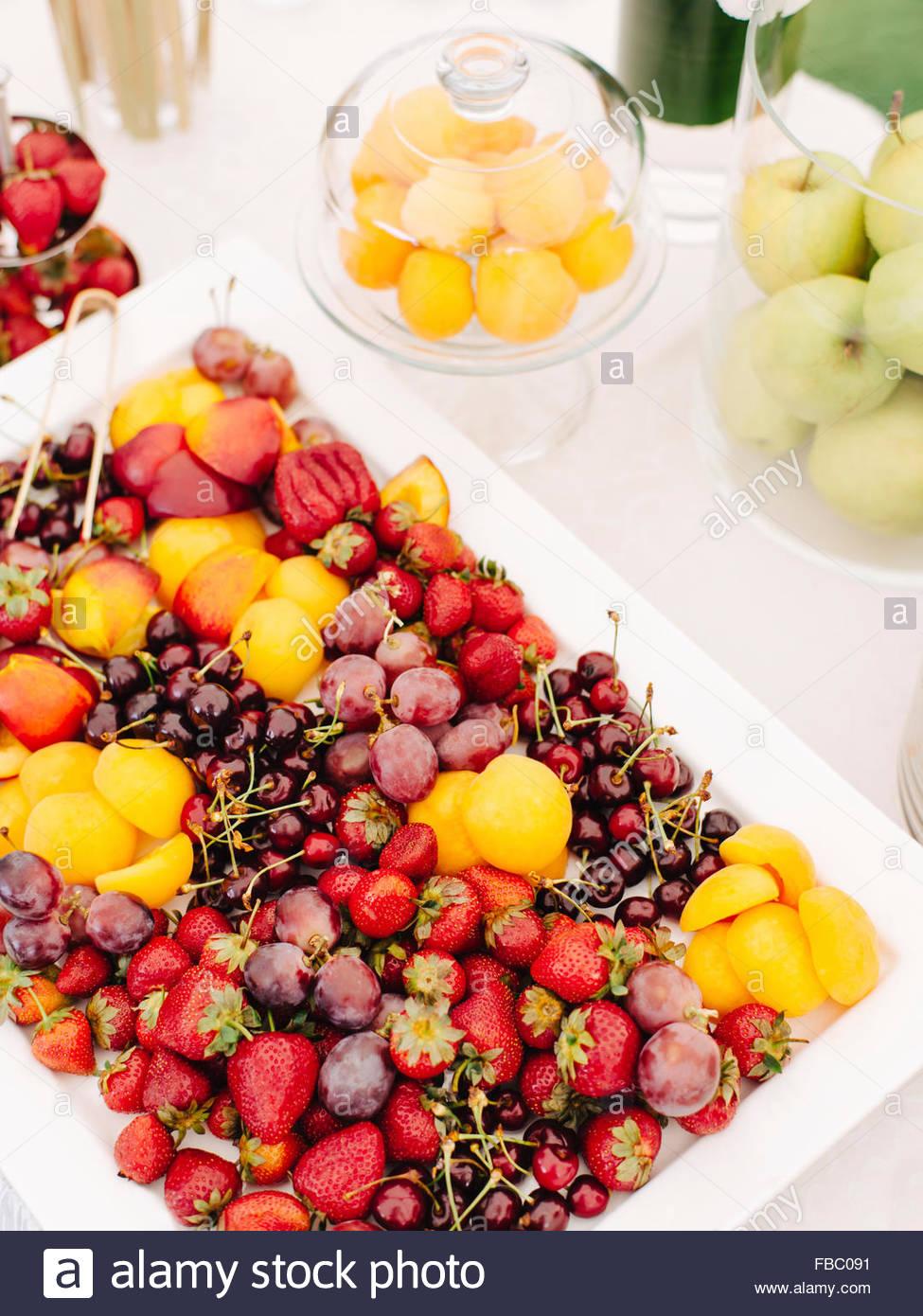 Piastra bianca con frutti e bacche sul tavolo per esterno Immagini Stock