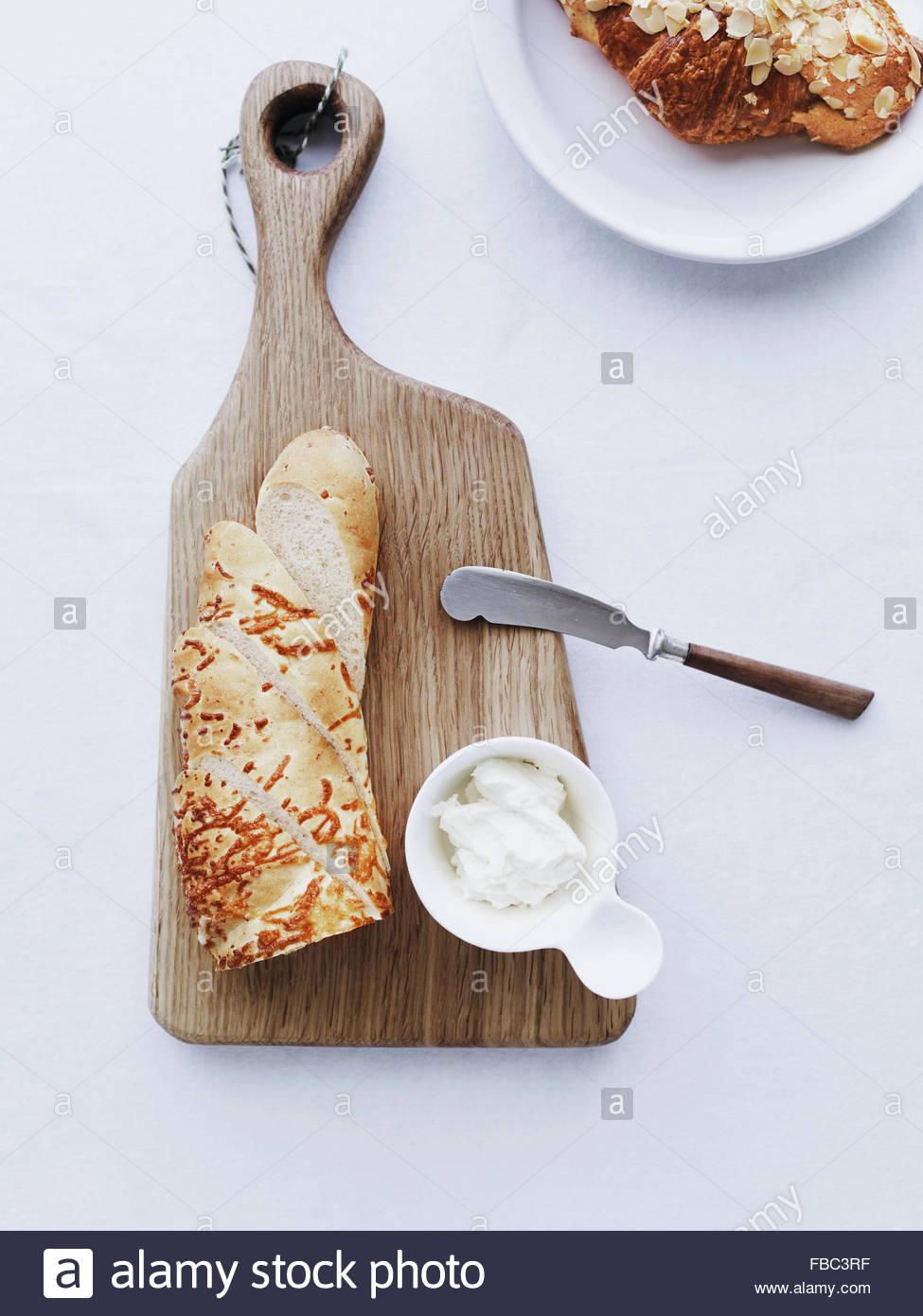 Baguette sul tagliere servita con crema di formaggio Immagini Stock
