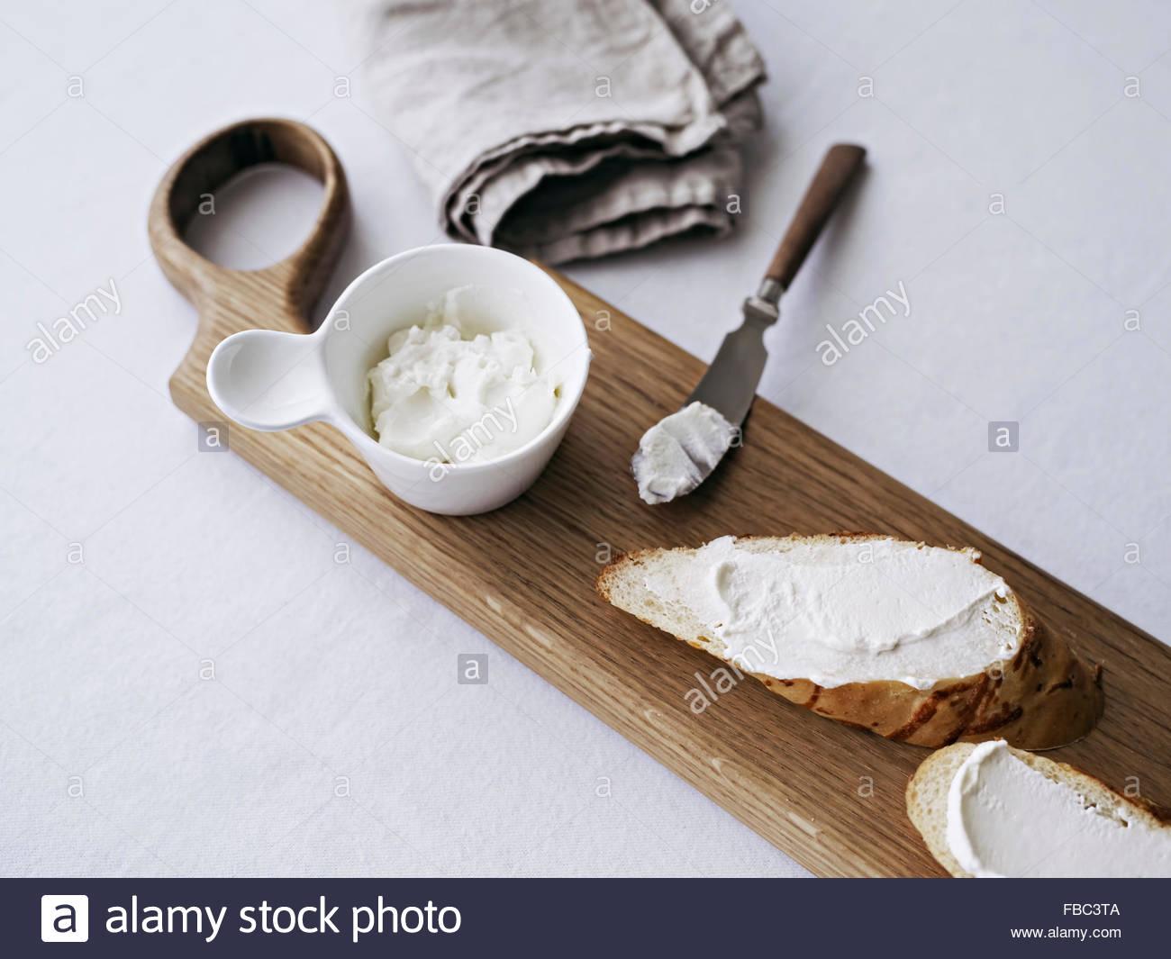 Pane sul tagliere servita con crema di formaggio Immagini Stock