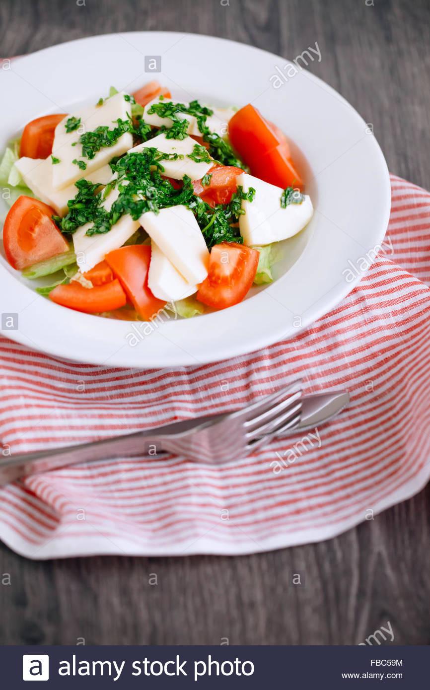 Angolo di alta vista di una fresca insalata con pomodoro, formaggio, basilico, prezzemolo e olio di oliva Immagini Stock