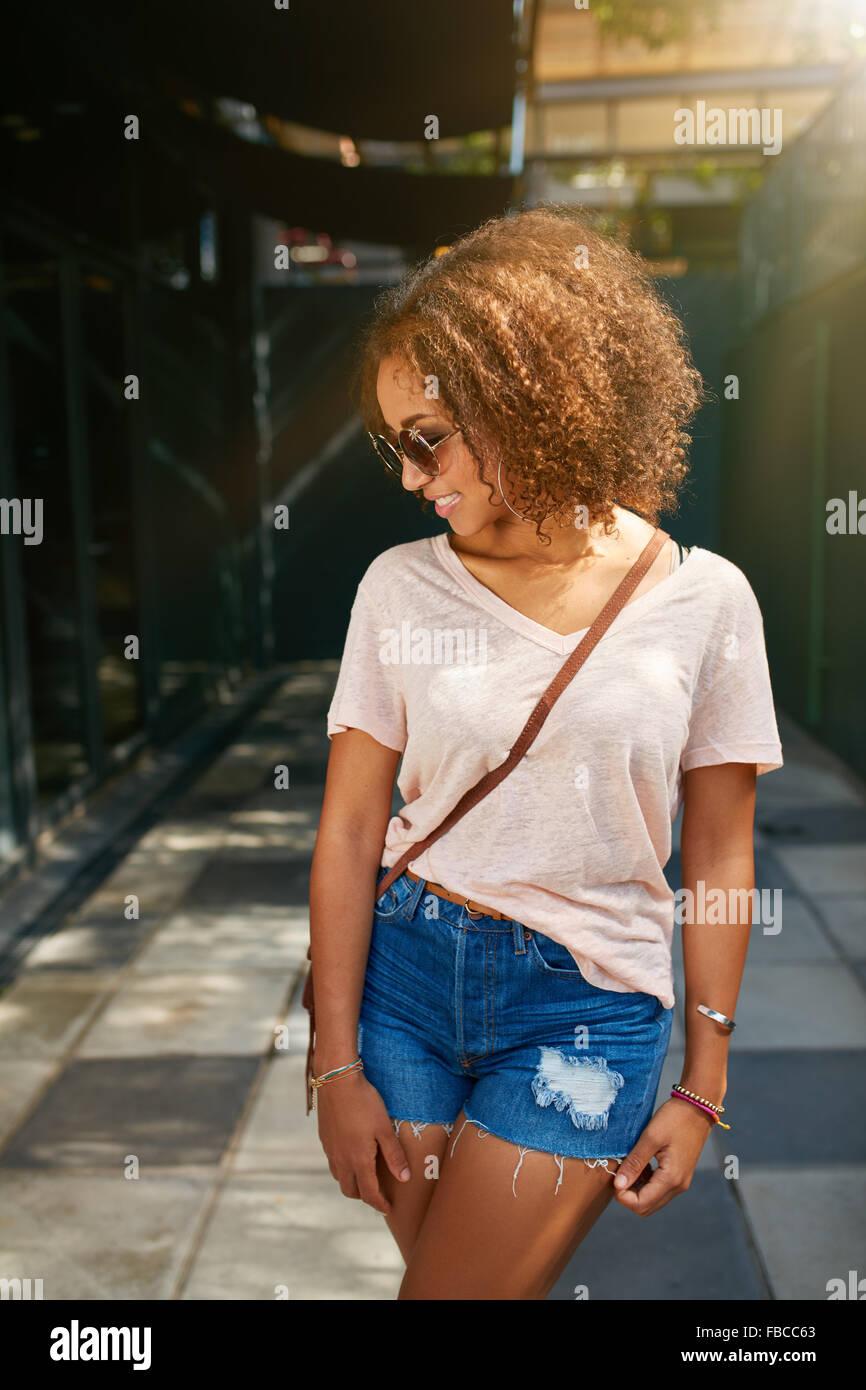 Giovane americano africano ragazza di città. Indossa abbigliamento casual, occhiali da sole e guardare verso il basso. Foto Stock