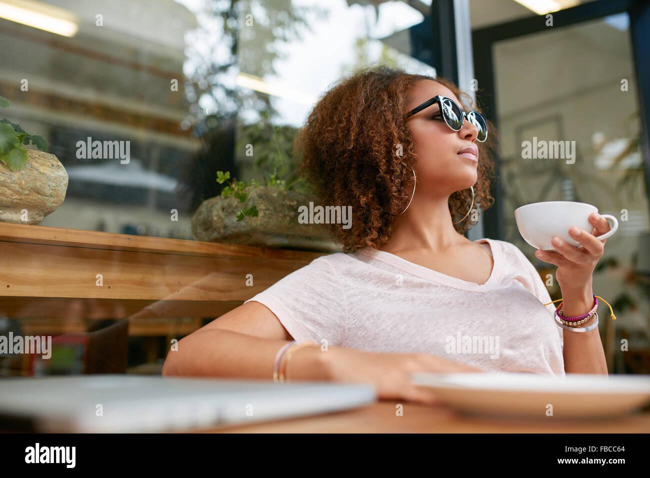 Ritratto di giovane attraente ragazza africana avente una tazza di caffè presso il cafe. Elegante ragazza di bere Foto Stock