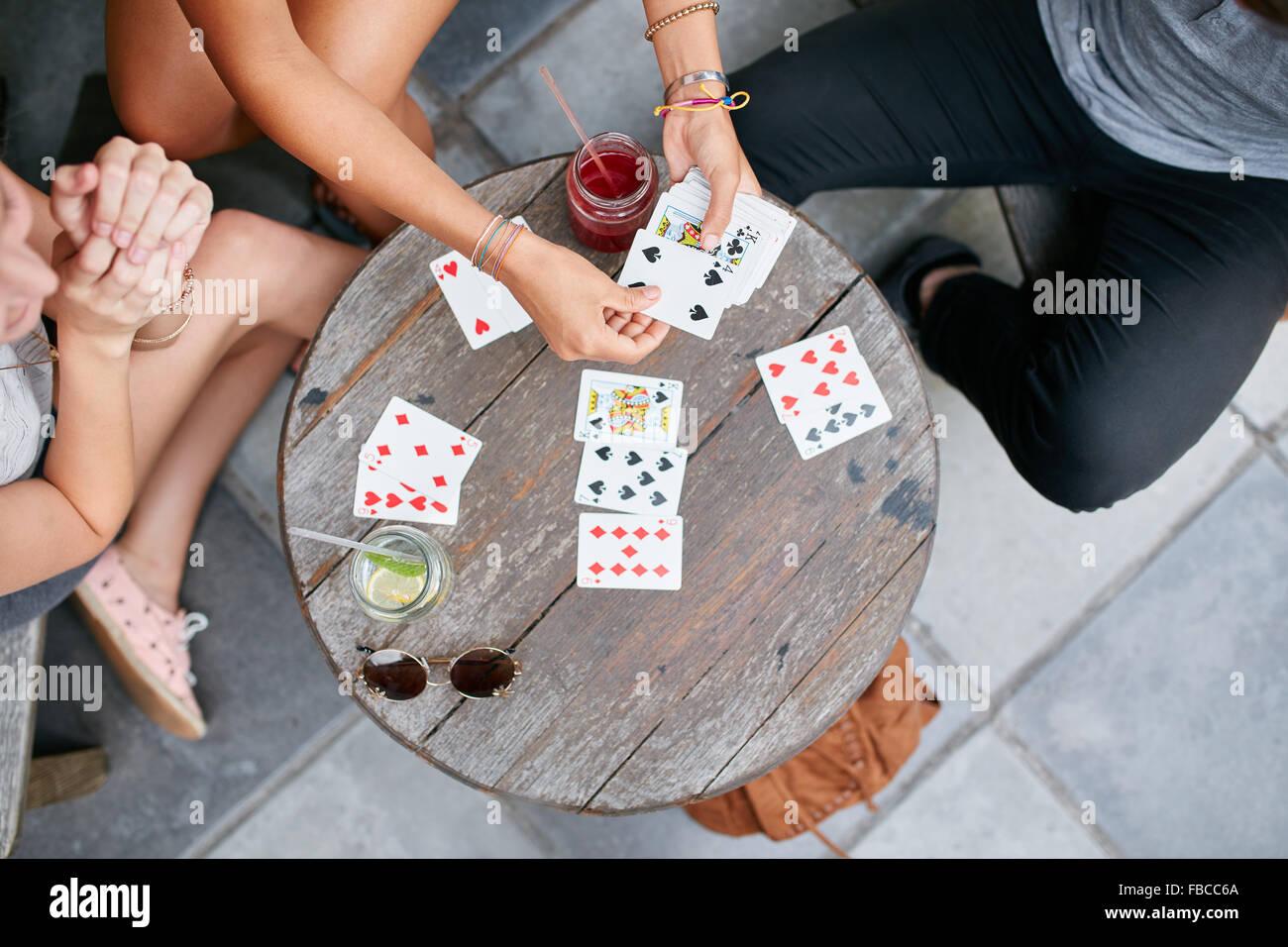 Vista superiore di tre giovani amici giocando a carte presso il cafe. I giovani a giocare gioco di carte presso Foto Stock