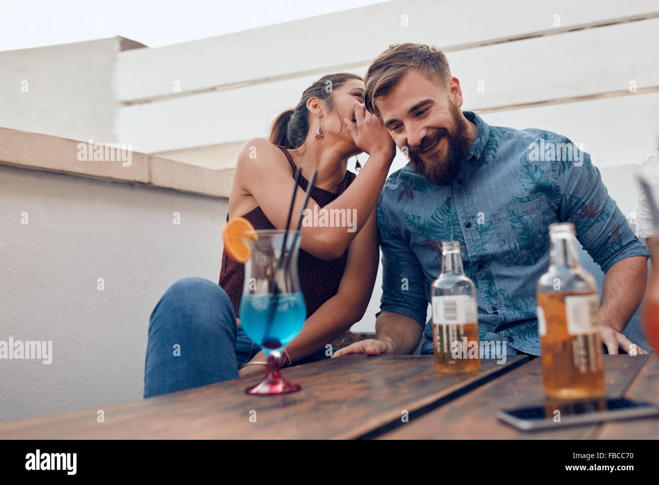 Due giovani seduti insieme spettegolare. Donna sussurra qualcosa nell'uomo le orecchie durante una festa. Immagini Stock