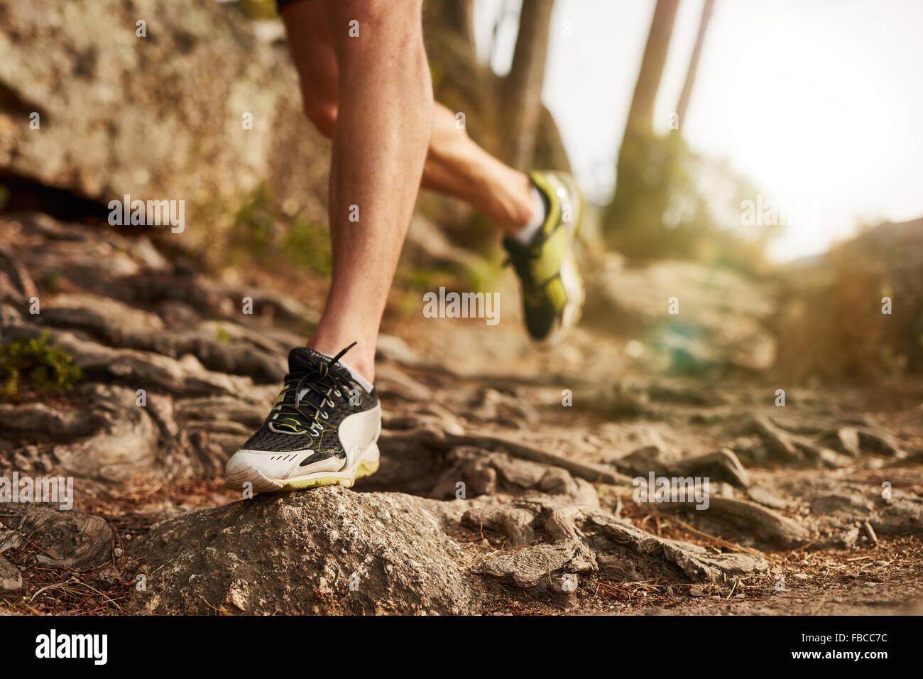 Close-up di trail running shoe sul difficile terreno roccioso. Runner maschio delle gambe del lavoro su terreni Immagini Stock