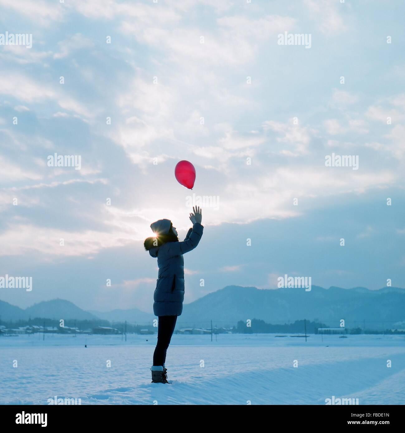 Vista laterale della ragazza in abiti caldi la cattura di palloncino rosso mentre si sta in piedi sul campo nevoso Foto Stock