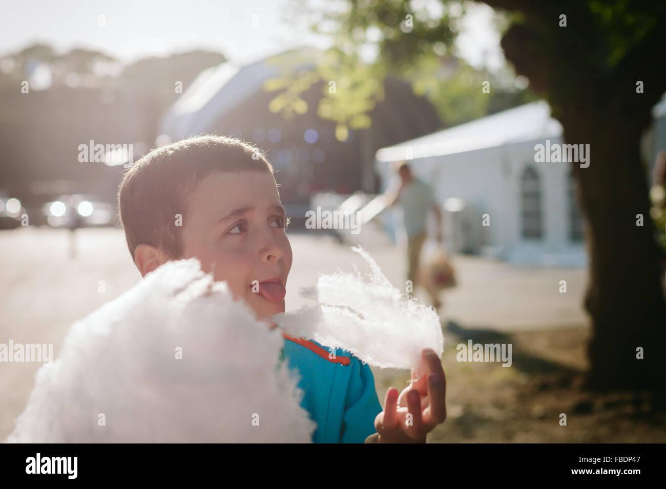 Boy Eating Candy Floss sulla giornata di sole Immagini Stock