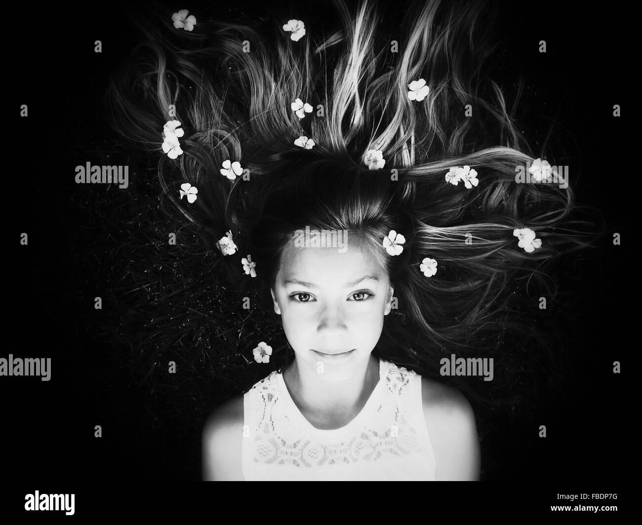 Ritratto di ragazza distesa verso il basso con i fiori nei capelli Immagini Stock