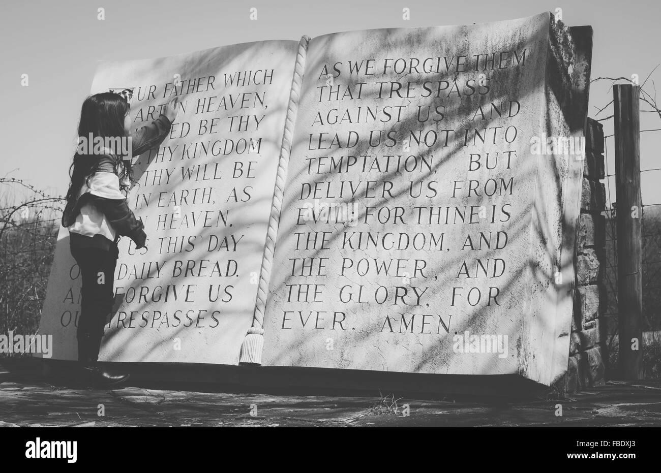 Vista posteriore della lettura della ragazza grande libro sacro Immagini Stock