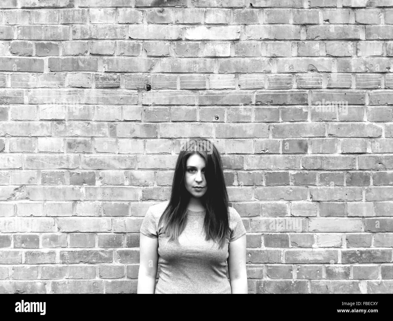 Ritratto di donna in piedi contro un muro di mattoni Immagini Stock