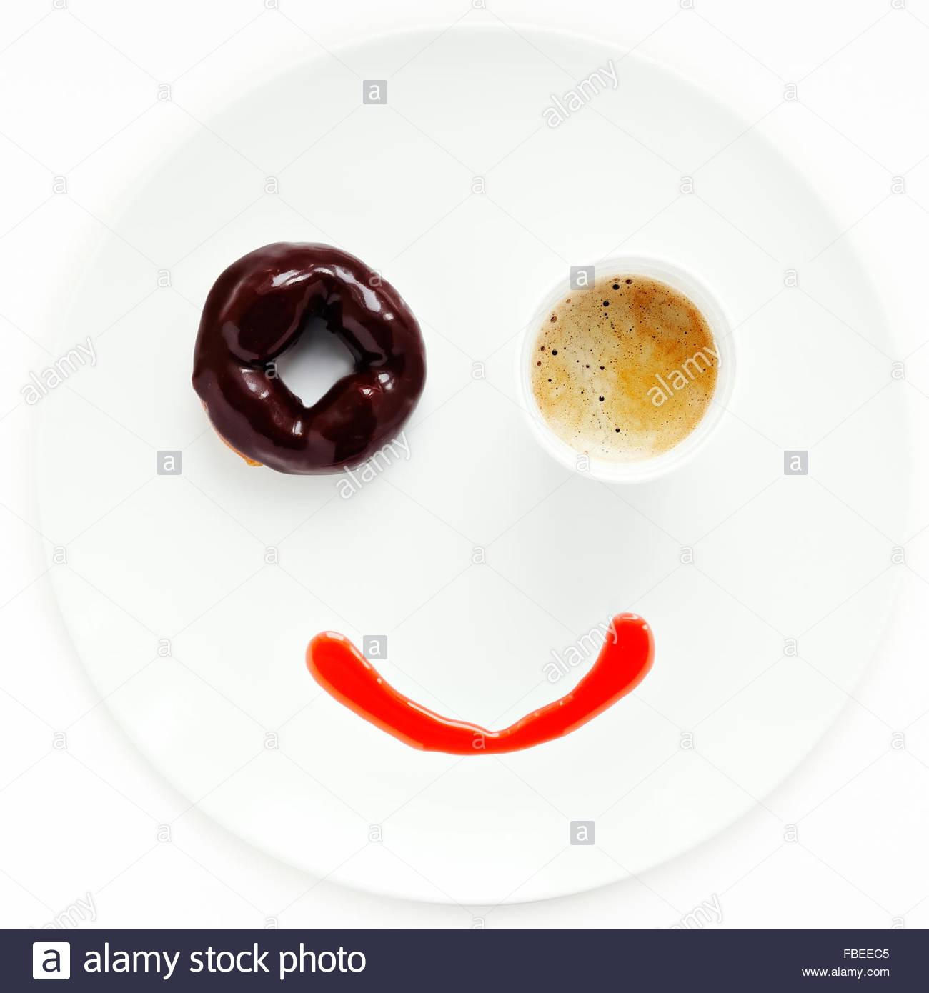 La faccina sorridente fatta di ciambella e la tazza di caffè sulla piastra Immagini Stock