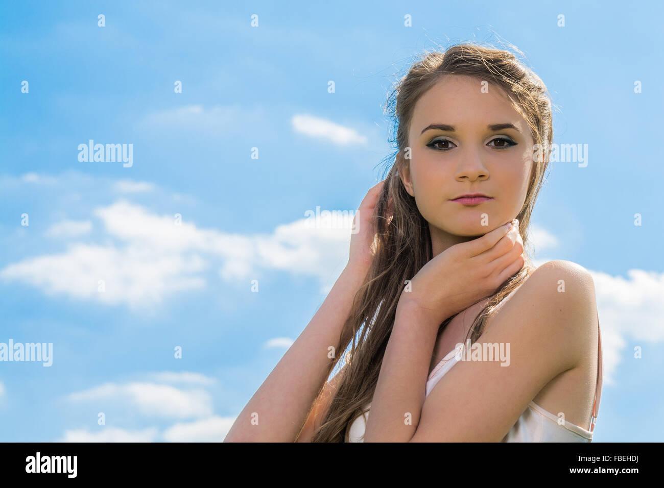 Basso angolo di vista Ritratto di giovane e bella donna che pongono contro Sky all'aperto Immagini Stock