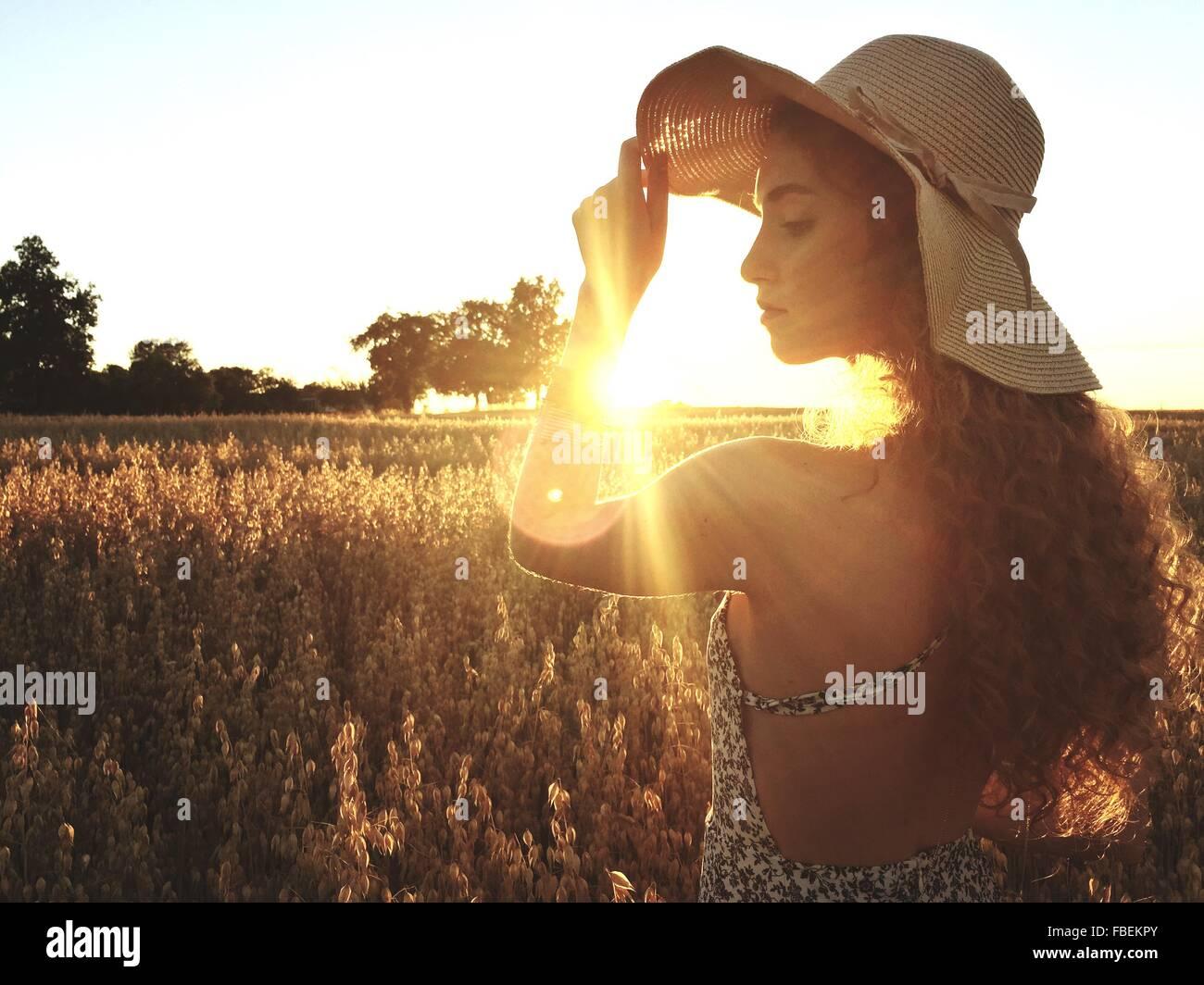 Bella donna in piedi sul campo contro il cielo chiaro durante il tramonto Immagini Stock