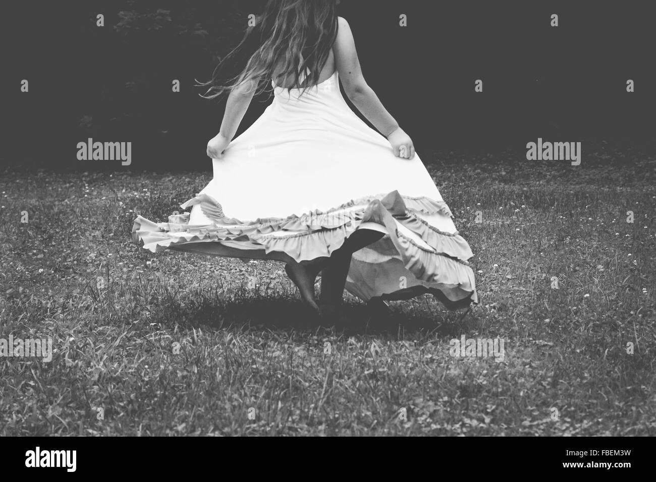 Vista posteriore della donna nel vestire camminando sul campo erboso Immagini Stock