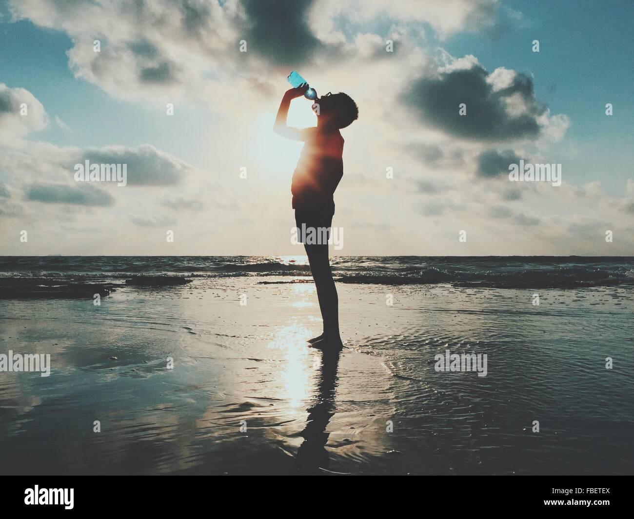 Vista laterale di uomo in piedi e acqua potabile a riva del mare contro il cielo nuvoloso Immagini Stock
