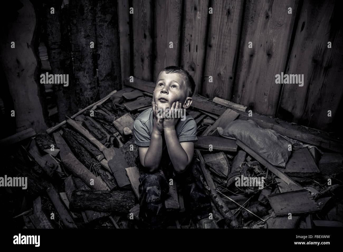 Angolo di Alta Vista di intrappolato ragazzo seduto sulle macerie in camera Immagini Stock