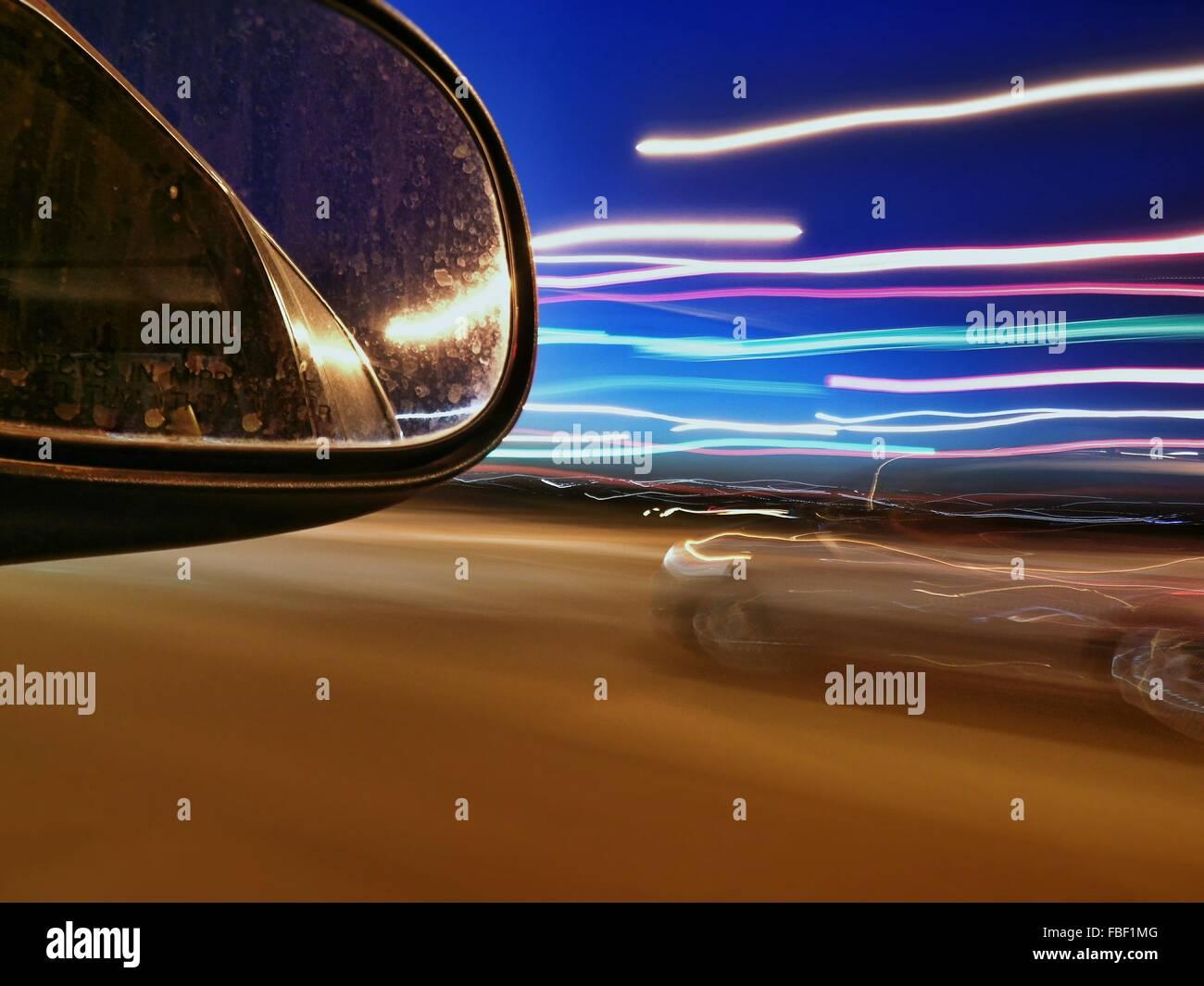 Specchio Side-View e sentieri di luce sulla strada di notte Immagini Stock