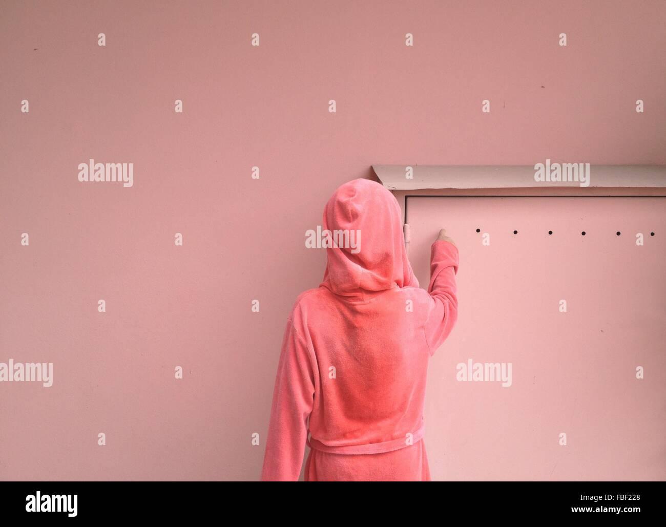 Vista posteriore della donna nel cofano contro la parete rosa Immagini Stock