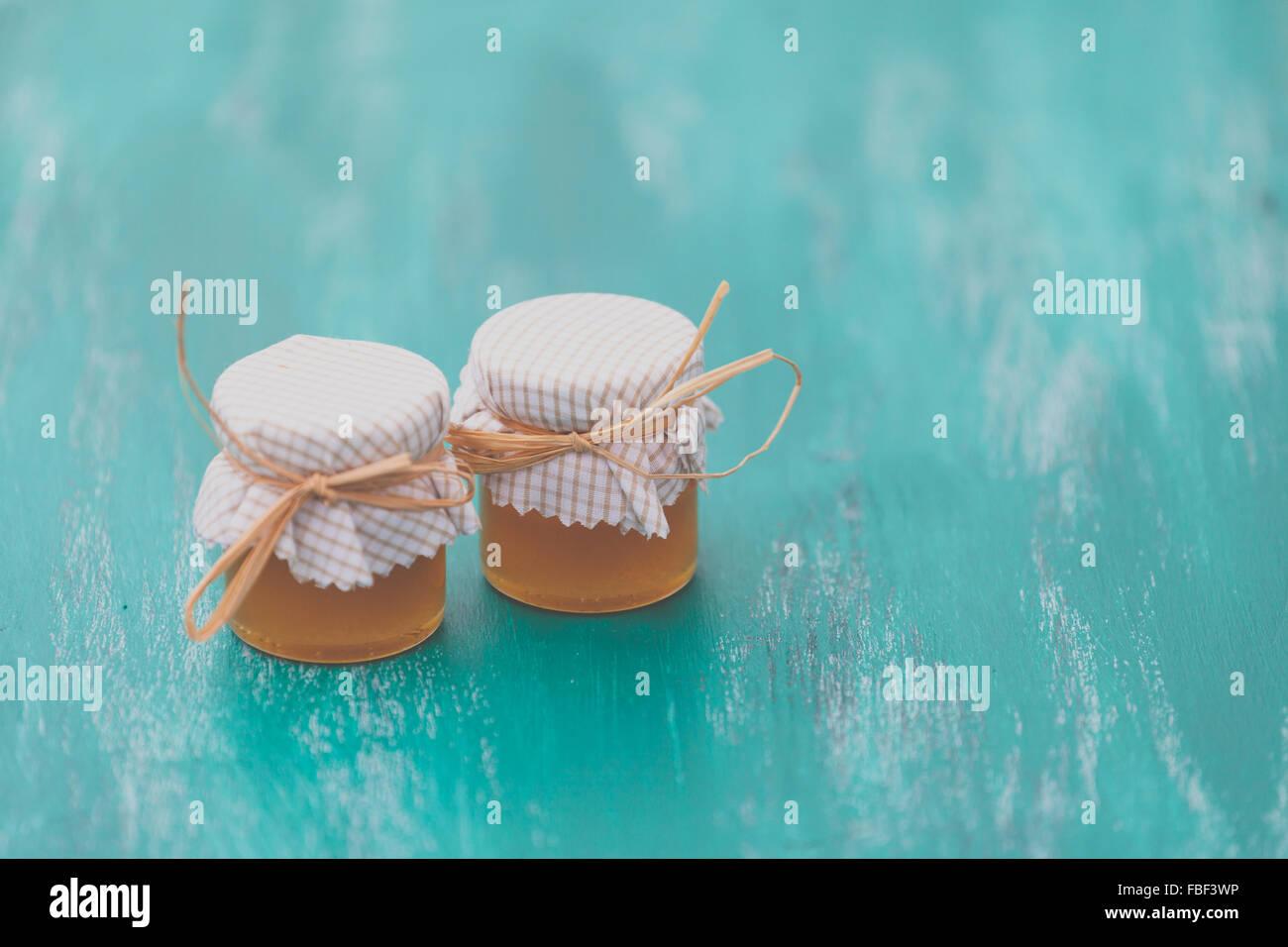 Close-Up di barattoli di miele ricoperti di tessuto sul tavolo Immagini Stock