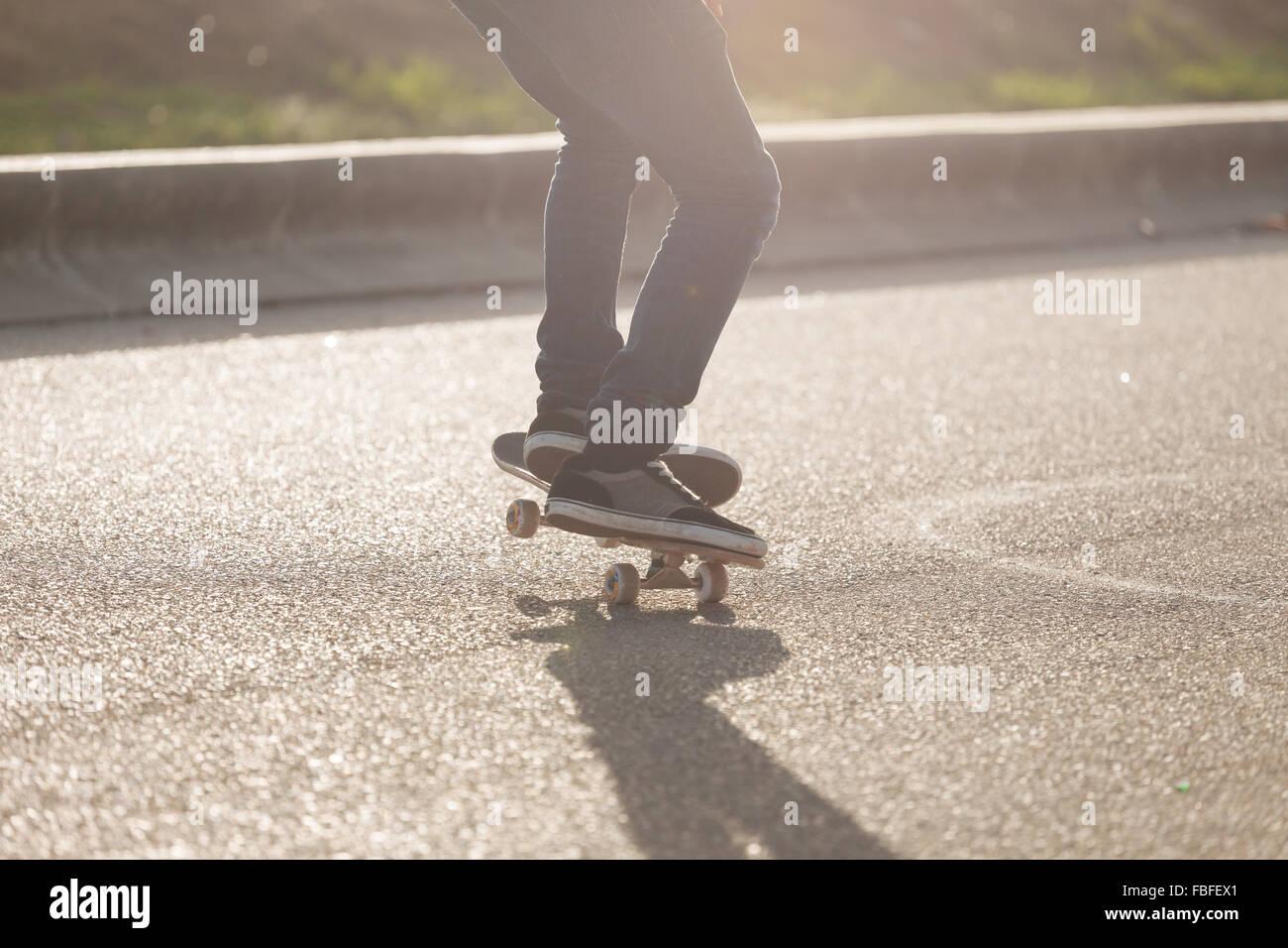 Sezione bassa dell'uomo lo skateboard sulla giornata di sole Immagini Stock