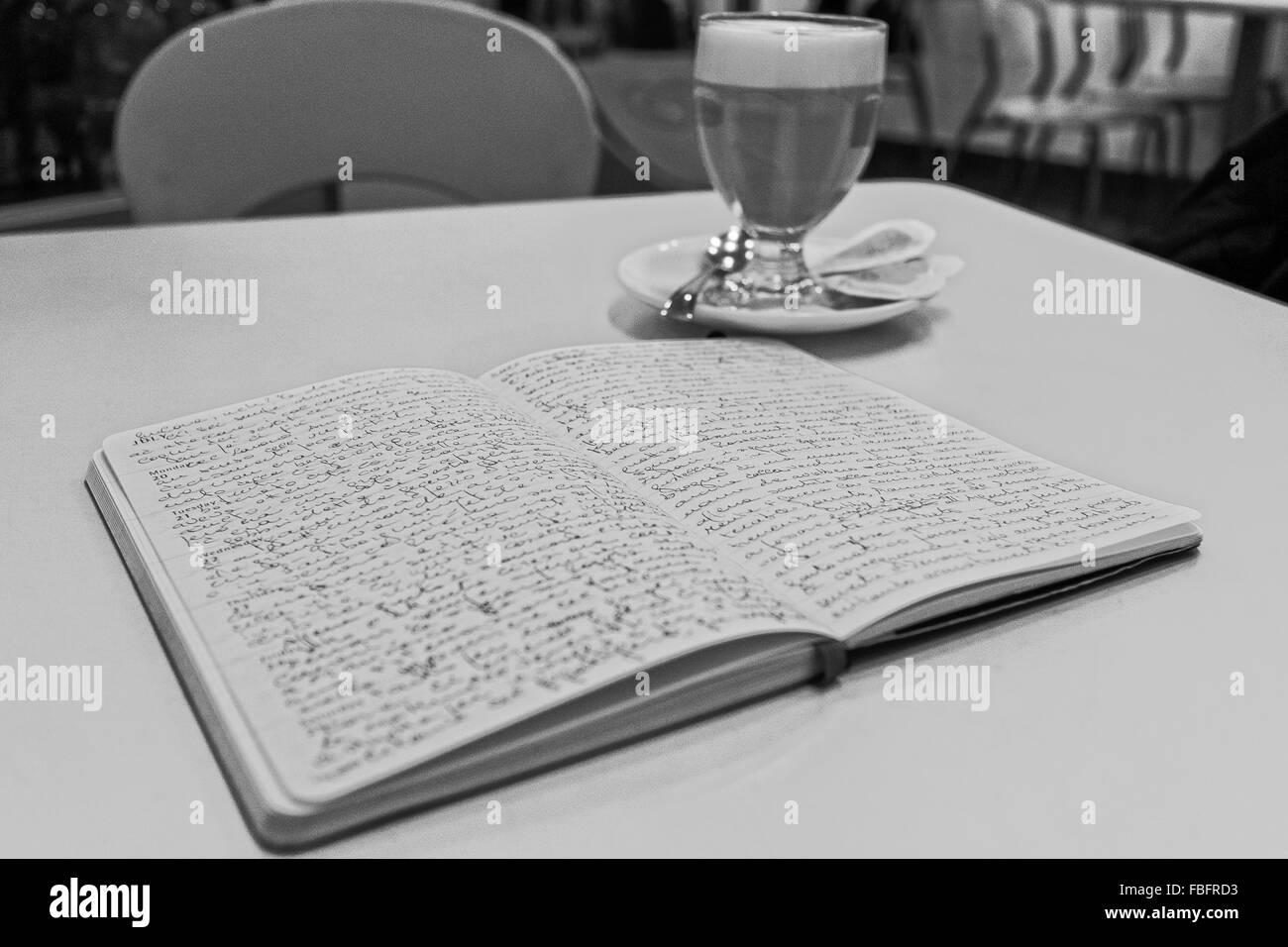 Svuotare tavolo e sedia con Apri diario moleskin riempito con la scrittura da parte di un autore accanto a bere Immagini Stock