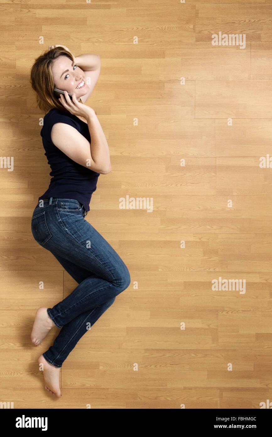 Donna sorridente giacente sul suo lato sinistro sul pavimento, appoggiata sul suo gomito, con il suo cellulare al Foto Stock