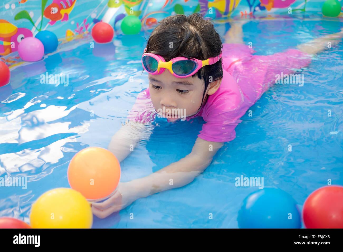 Una bambina in rosa tuta la riproduzione di acqua e sfere in blu la piscina per bambini Foto Stock