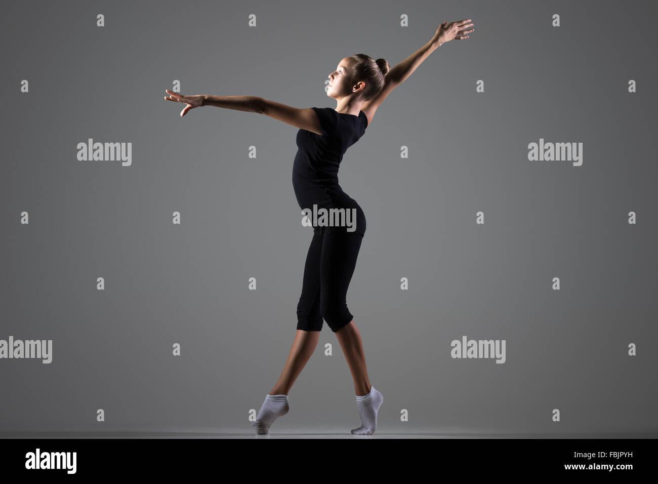 Bella giovane montare ginnasta atleta donna in abbigliamento sportivo che lavora fuori, ballare sulla tiptoes, fare Immagini Stock