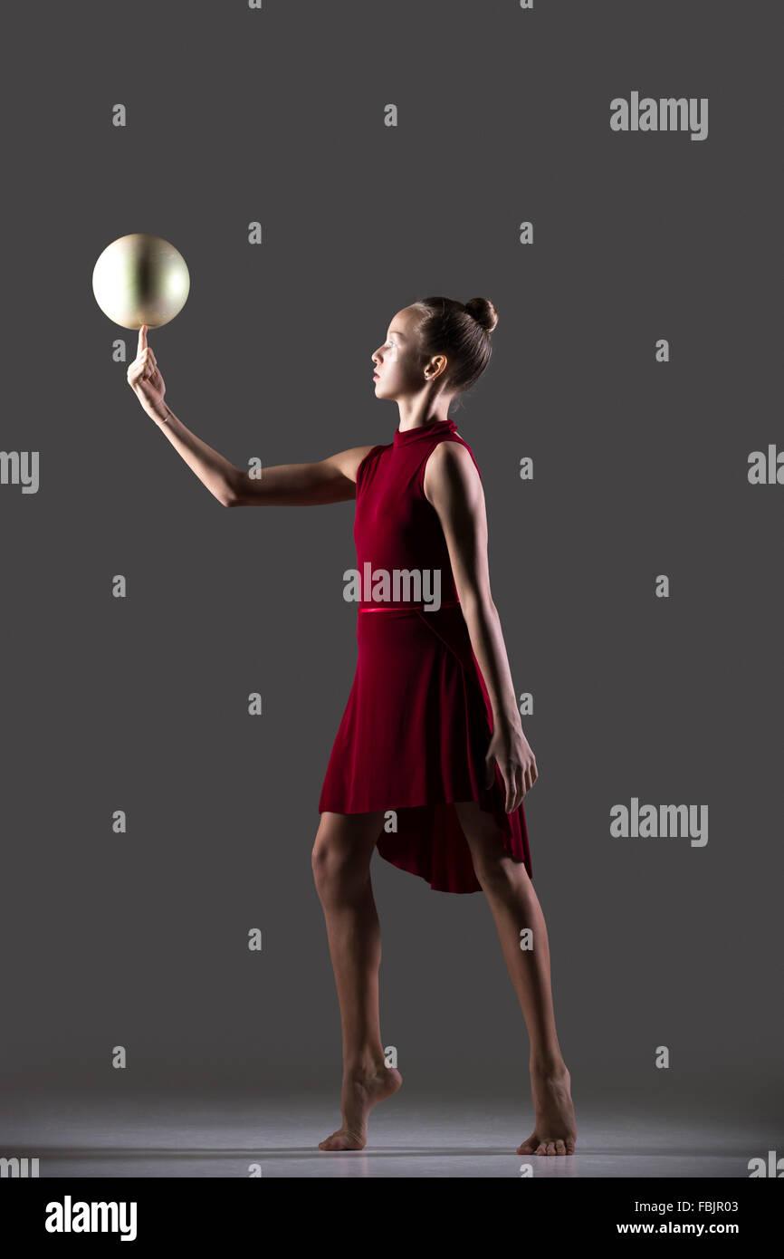 Bella giovane montare ginnasta atleta donna abbigliamento sportivo in abito rosso che lavora fuori, facendo ginnastica Immagini Stock