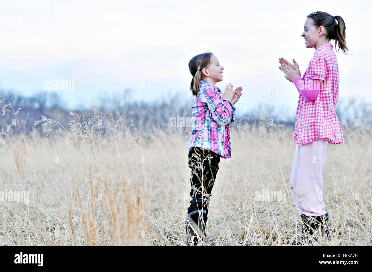 Le ragazze a giocare battendo le mani mano giochi nel campo Immagini Stock