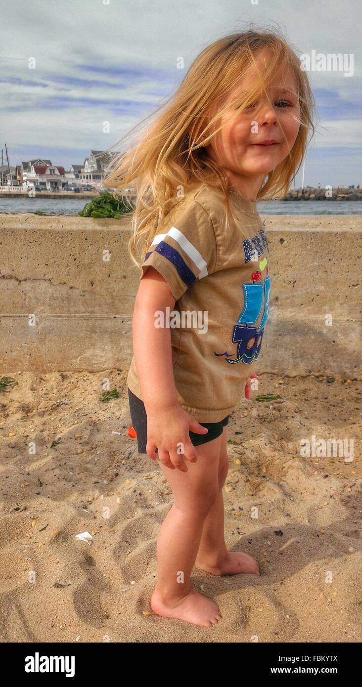 A piena lunghezza Ritratto di una ragazza in piedi sulla spiaggia Immagini Stock