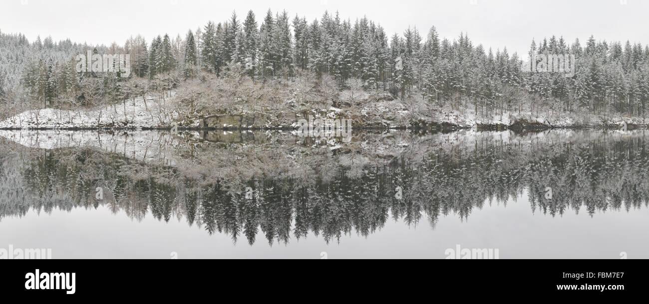 Loch Ard inverno riflessioni panorama - una leggera spolverata di neve e ancora acqua creando dettagliatissime riflessioni Immagini Stock