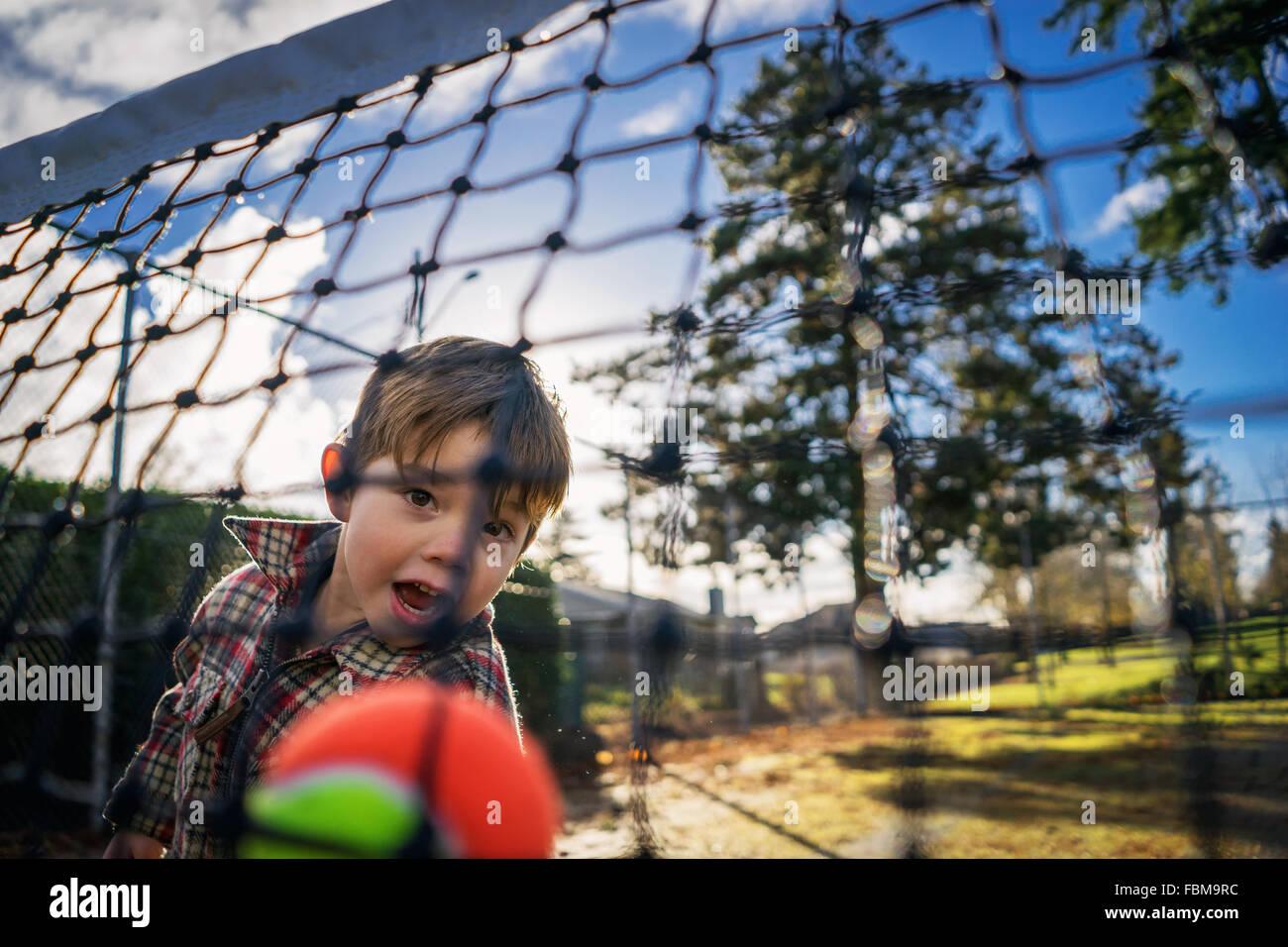 Vista attraverso una rete di un ragazzino gettando palla da tennis Immagini Stock