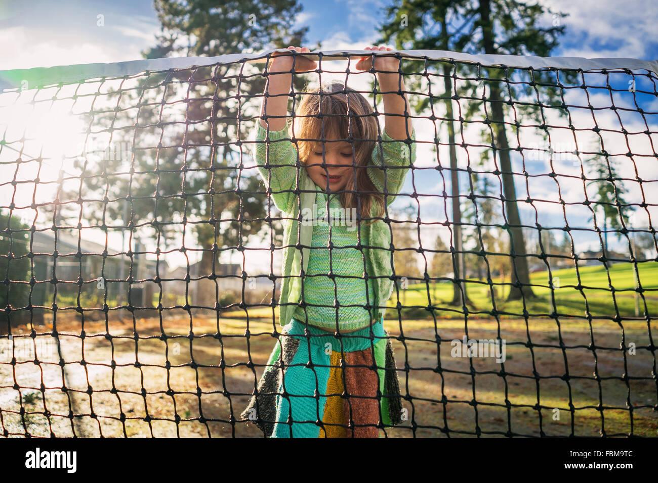 Ragazza in piedi sul campo da tennis net di sollevamento Immagini Stock