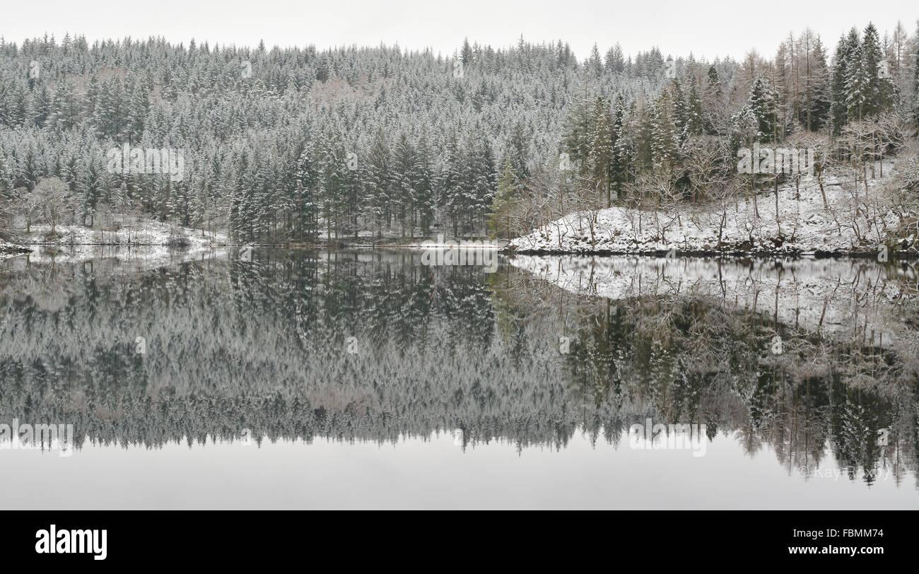 Loch Ard inverno riflessioni dopo la nevicata - una leggera spolverata di neve e ancora acqua creando dettagliatissime Immagini Stock