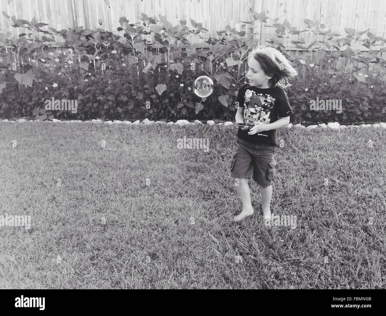 Carino il ragazzo in piedi sul campo erboso Immagini Stock