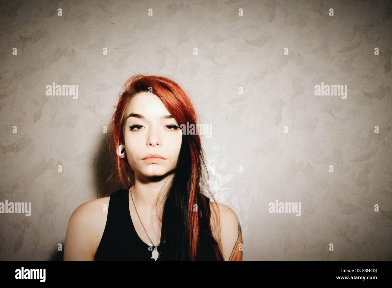 Giovane donna in piedi contro la parete Immagini Stock