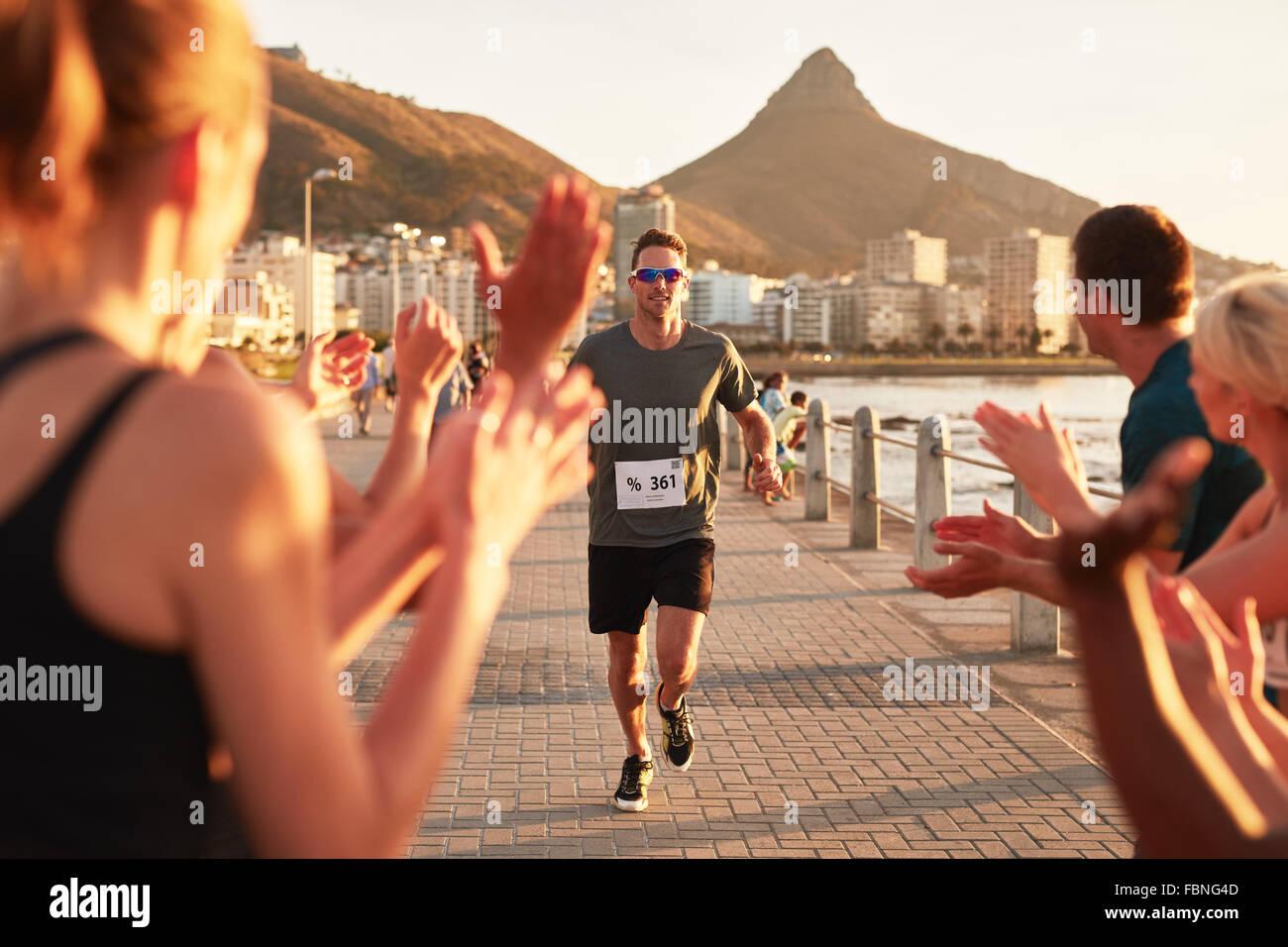 Giovane atleta maschio essendo applaudito dai sostenitori come egli raggiunge il traguardo di una gara di corsa. Immagini Stock