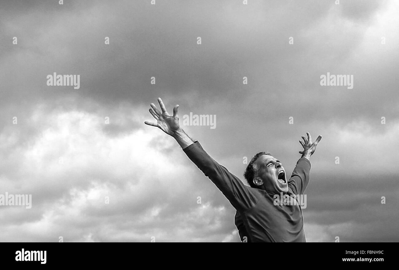 L'uomo grida a braccia alzate Immagini Stock