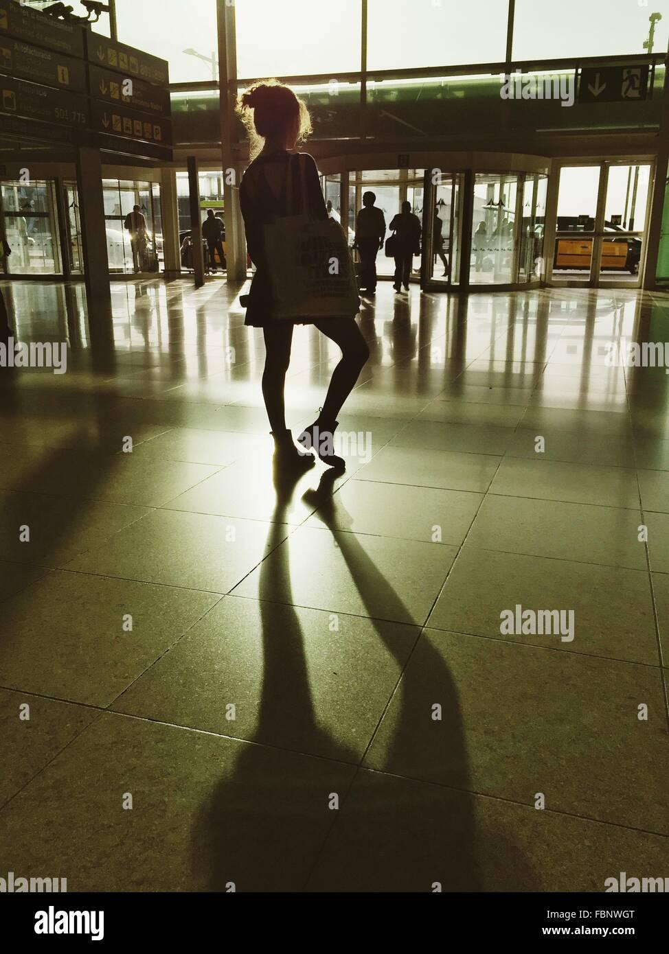 Vista posteriore della giovane donna in piedi all'aeroporto Immagini Stock