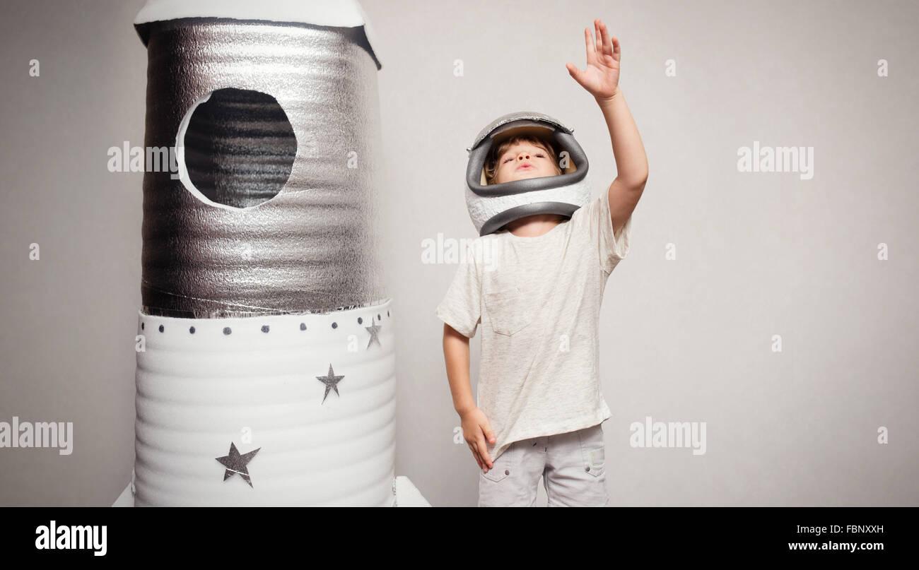 Bambino felice vestito in un costume da astronauta giocando con la mano ma Immagini Stock